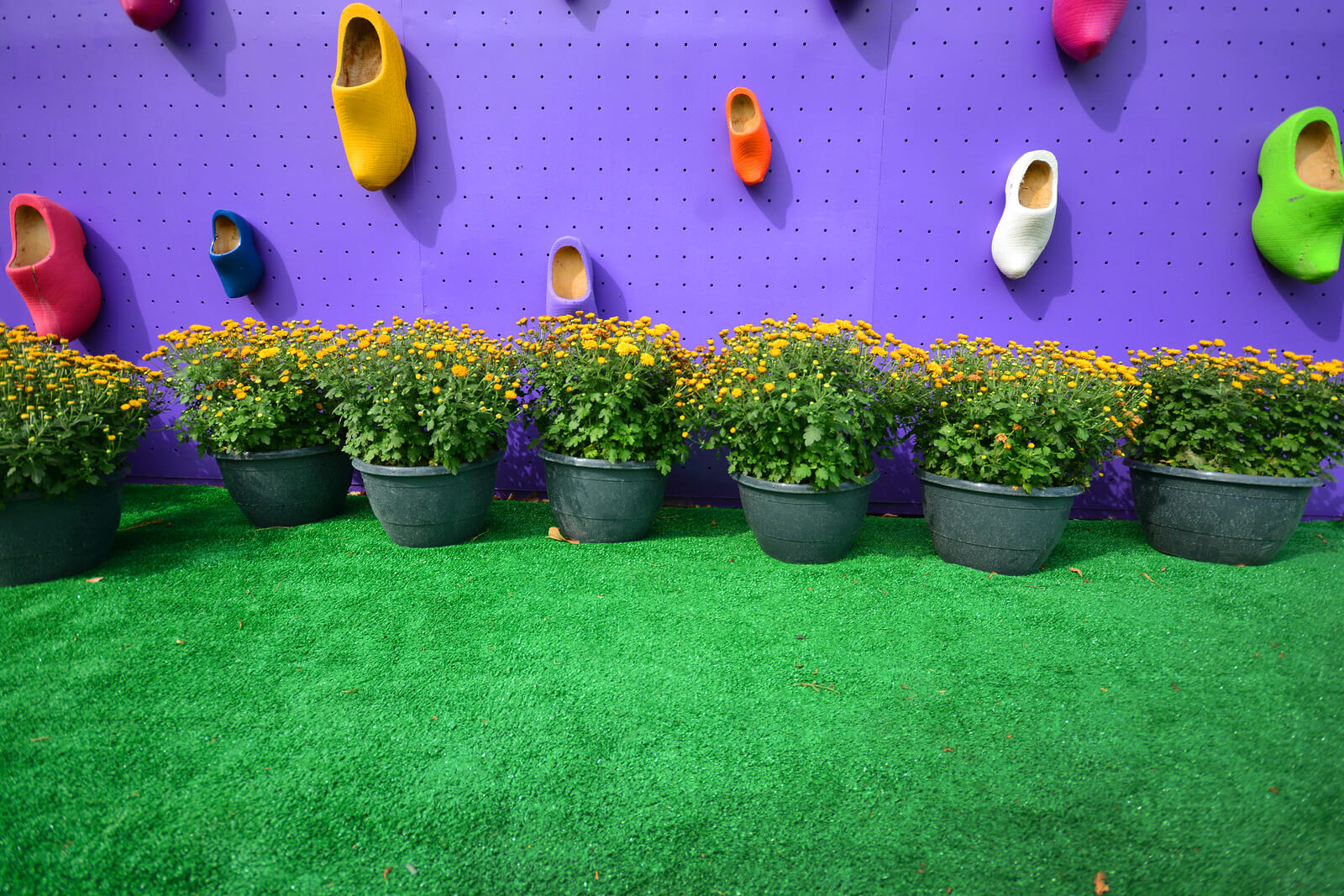 Landscape design background with artificial grass, flowerpots and decorative boots.